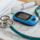 glucometer and stethoscope on clipboard
