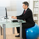 Man sitting at desk on an exercise ball